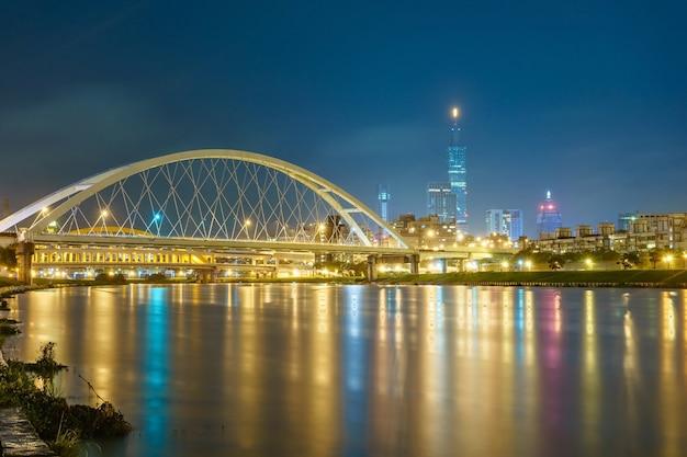 Nachtlandschaft von taipeh-stadt mit schönen reflexionen von wolkenkratzern u. von brücken an der dämmerung. Premium Fotos