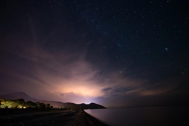 Nachtsternenklarer himmel an der seeküste Premium Fotos