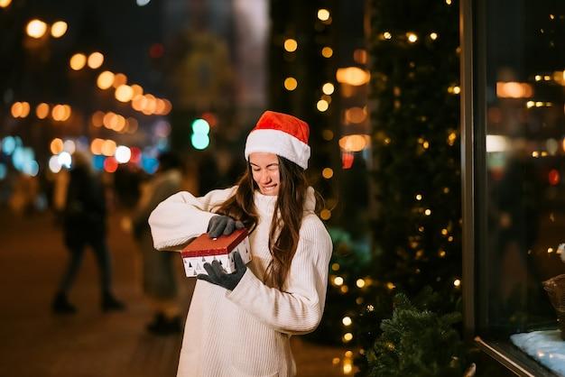 Nachtstraßenporträt der jungen schönen frau, die begeistert handelt. festliche girlandenlichter. Kostenlose Fotos