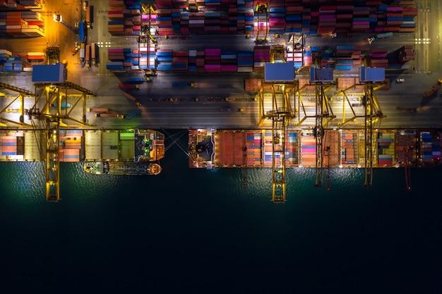 Nachtszene be- und entladen von containerschiffen im tiefseehafen luftaufnahme des imports und exports von frachttransporten per containerschiff auf offener see durch den unternehmensdienst und die industriefrachtlogistik Premium Fotos