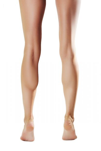 Nackte weibliche beine auf zehenspitzen, hinterer gesichtspunkt Premium Fotos