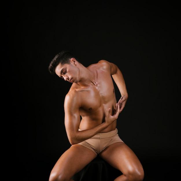 Nackter auf faltenden armen des stuhls und verbiegendem torso. Kostenlose Fotos