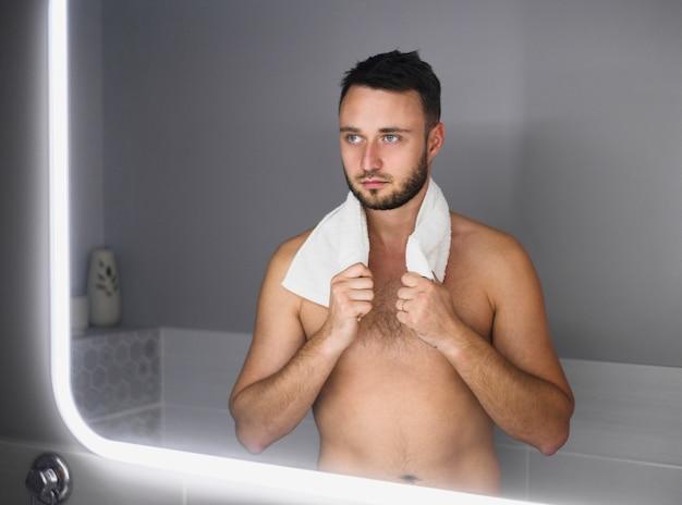 Nackter junger mann, der im spiegel schaut Kostenlose Fotos