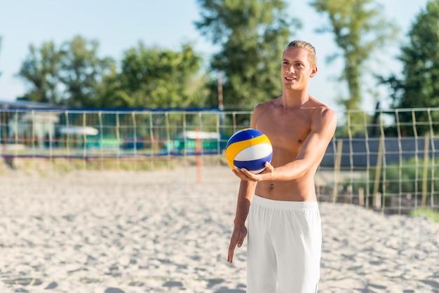 Nackter oberkörper männlicher volleyballspieler am strand, der ball hält Kostenlose Fotos