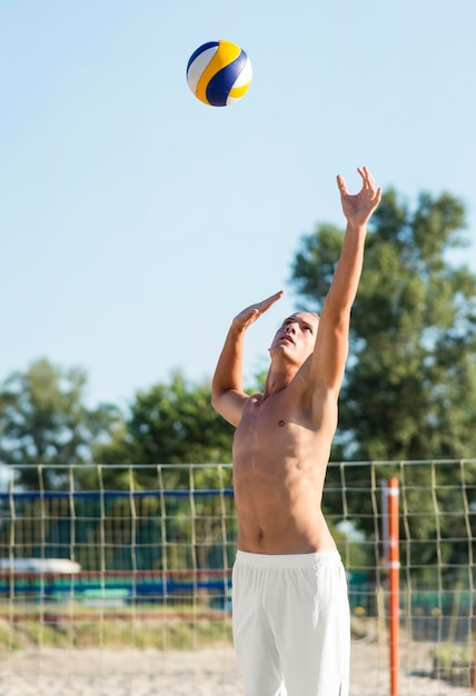 Nackter oberkörper männlicher volleyballspieler am strand, der mit ball spielt Kostenlose Fotos