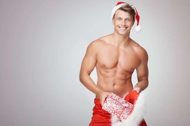 Nackter oberkörper mann, der einige weihnachtsgeschenke einfügt Kostenlose Fotos