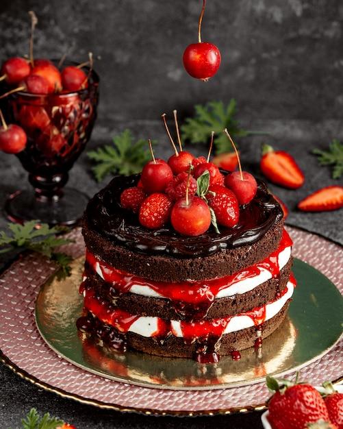 Nackter schokoladenkuchen, dekoriert mit kleinen erdbeer-himbeer-äpfeln und sirup Kostenlose Fotos