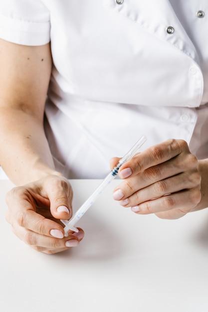 Nadel in arzt- oder kosmetikerhänden in blauen handschuhen. Premium Fotos