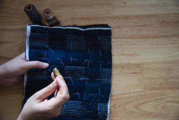 Nähender stoff der weinlesefrau eigenhändig mit stickerei stellte auf holztisch - leute und handgemachtes diy hausarbeitkonzept ein Kostenlose Fotos