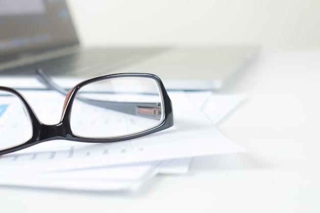 Näher an den brillen von geschäftsleuten auf dem finanzdiagramm auf einem modernen weißen schreibtisch. Premium Fotos