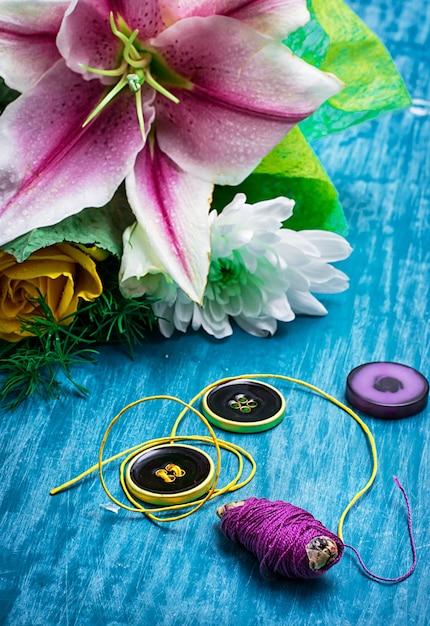 Nähzubehör mit einem blumenstrauß frischer blumen auf türkishintergrund Premium Fotos