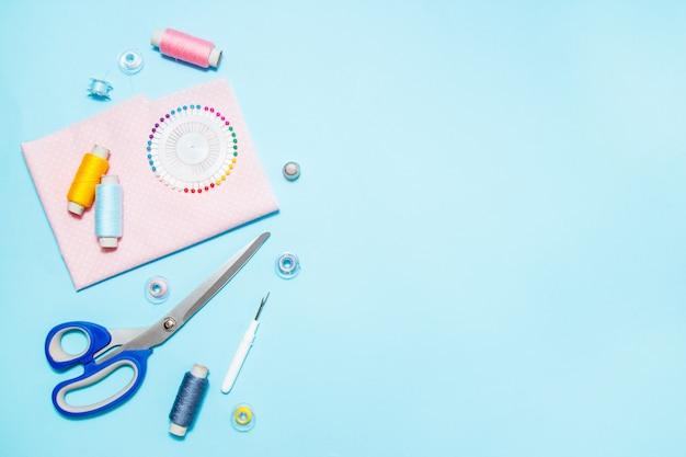 Nähzubehör, muster und zubehör für handarbeiten auf blauem hintergrund, nähen, stickerei. platz für text. flach lag, ansicht von oben. Premium Fotos