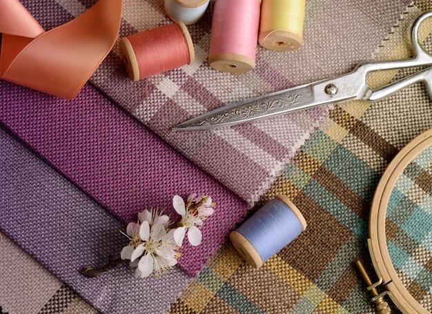 Nähzubehör, nadeln, vintage-schere auf dem bunten sackleinen-textil Premium Fotos