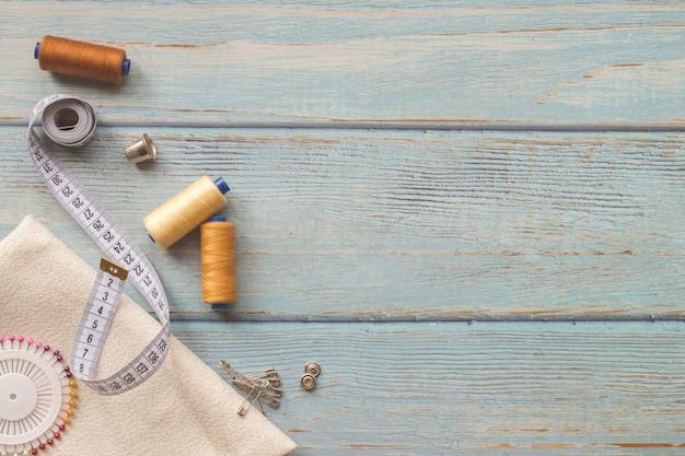 Nähzubehör und stoff auf blauem grund. stoff, nähgarne, nadel, knöpfe und nähzentimeter. draufsicht, flatlay, copyspace Premium Fotos