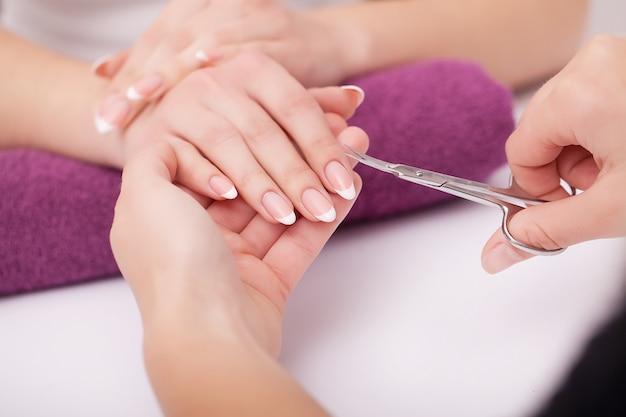 Nagelpflege und maniküre. nahaufnahme von den schönen weiblichen händen, die transparenten nagellack auf den nägeln der gesunden natürlichen frau im schönheitssalon auftragen. nägel des manikürist-handmalerei-kunden. hohe auflösung Premium Fotos