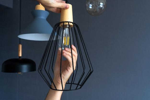Nahansicht. eine hand wechselt eine glühbirne in einer stilvollen loftlampe. spiralfadenlampe. moderne inneneinrichtung. Premium Fotos
