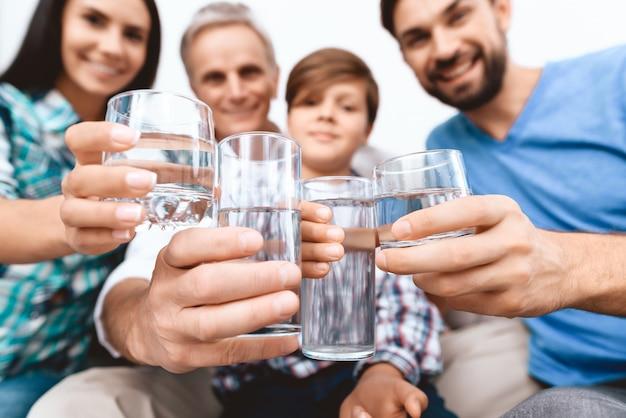 Nahansicht. freundliche familie, die mit gläsern wasser zujubelt. Premium Fotos