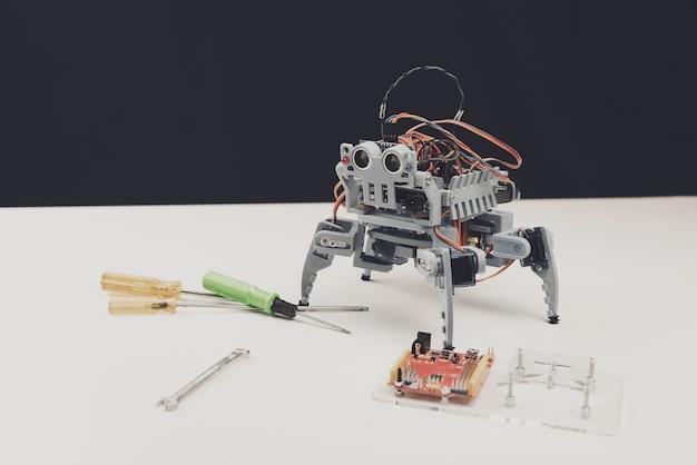 Nahansicht. kleiner grauer roboter mit werkzeugen auf tabelle. Premium Fotos