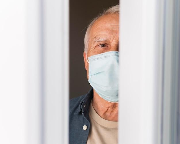 Nahaufnahme alter mann mit maske drinnen Kostenlose Fotos