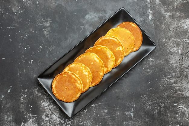 Nahaufnahme ansicht von hausgemachten pfannkuchen auf einem quadratischen schwarzen teller auf grau aufgereiht Kostenlose Fotos
