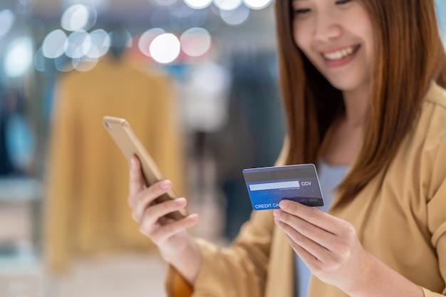Nahaufnahme-asiatin, die kreditkarte mit mobile für das on-line-einkaufen im kaufhaus verwendet Premium Fotos