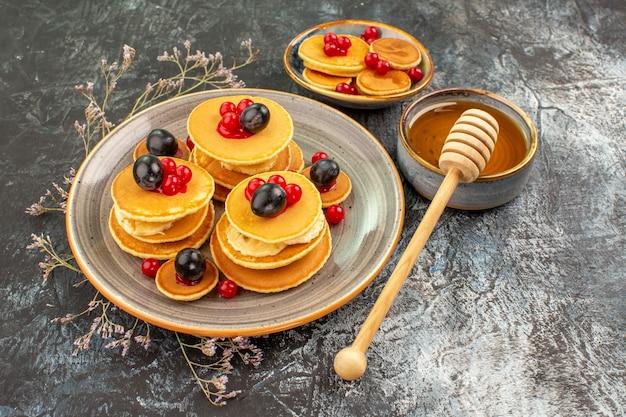 Nahaufnahme der ansicht von fruchtpfannkuchen auf einem kleinen und großen teller mit honig Kostenlose Fotos
