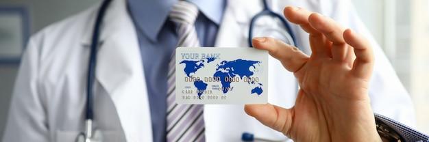 Nahaufnahme der arzthand, die plastikkreditbankkarte hält. praktizierender in uniform mit stethoskop. zahlungsmethode für dienstleistungen in privatkliniken. medizin- und krankenversicherungskonzept Premium Fotos
