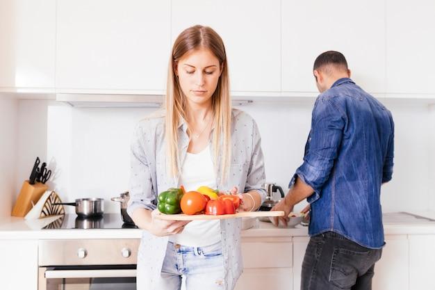 Nahaufnahme der blonden jungen frau, die in der hand bunten grünen pfeffer mit ihrem ehemann am hintergrund hält Kostenlose Fotos