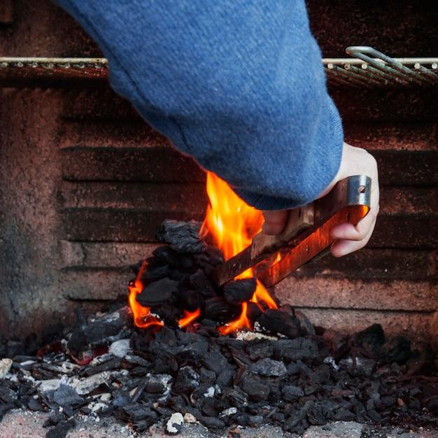 Nahaufnahme der brennenden kohle eines mannes hand im grill Kostenlose Fotos