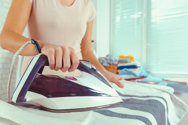 Nahaufnahme der bügelnden kleidung der frau auf bügelbrett Premium Fotos