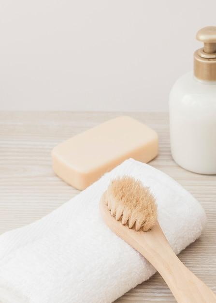Nahaufnahme der bürste; handtuch; seife und kosmetikflasche auf holzoberfläche Kostenlose Fotos