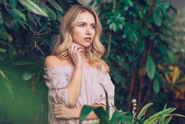 Nahaufnahme der durchdachten blonden jungen frau, die im garten weg schaut steht Kostenlose Fotos