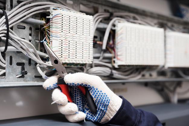 Nahaufnahme der elektrikerhand, die elektrischen kabeldraht mit einer zange schneidet Kostenlose Fotos