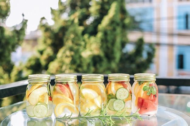 Nahaufnahme der erfrischenden getränke mit früchten in einem glas auf dem tisch unter dem sonnenlicht Kostenlose Fotos