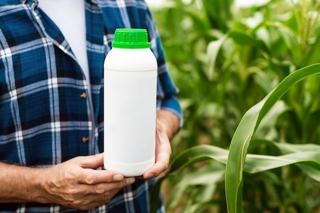 Nahaufnahme der flasche mit mineraldünger in den männlichen händen des landwirts - bild Premium Fotos