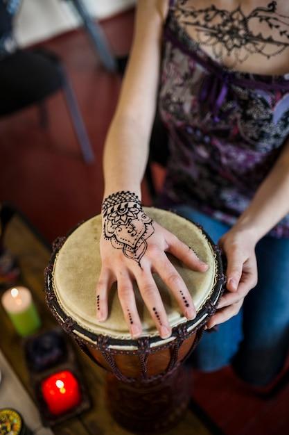 Nahaufnahme der frau bongotrommel mit mehndi tätowierung auf ihrer hand spielend Kostenlose Fotos
