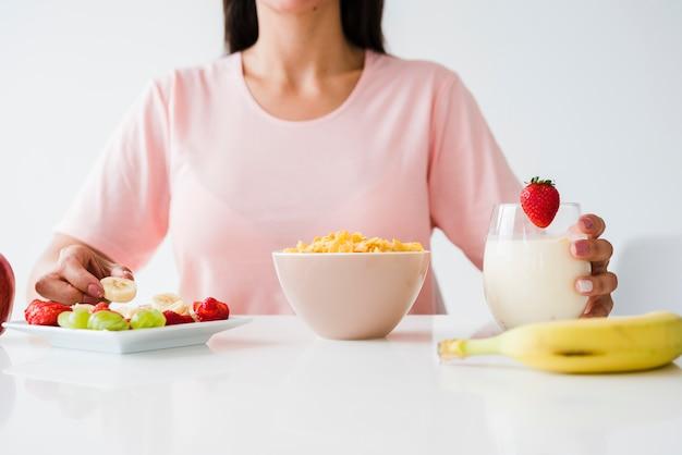 Nahaufnahme der frau, die gesundes auf weißem schreibtisch frühstückt Kostenlose Fotos