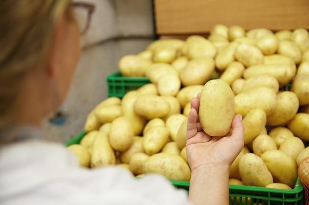 Nahaufnahme der frau, die kartoffel in der hand hält Kostenlose Fotos