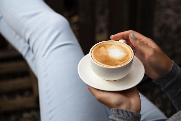 Nahaufnahme der frau kaffeetasse und platte halten Kostenlose Fotos