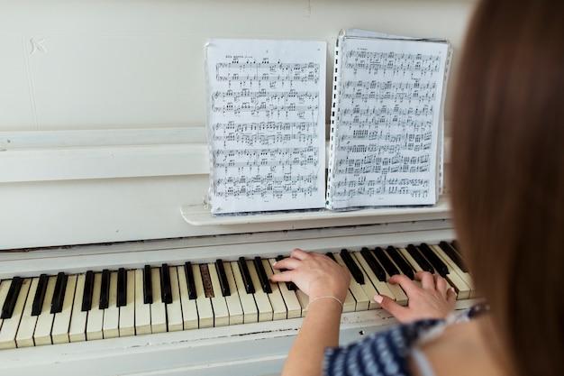 Nahaufnahme der frau klavier spielend, indem sie musikalisches blatt auf klavier betrachtet Kostenlose Fotos