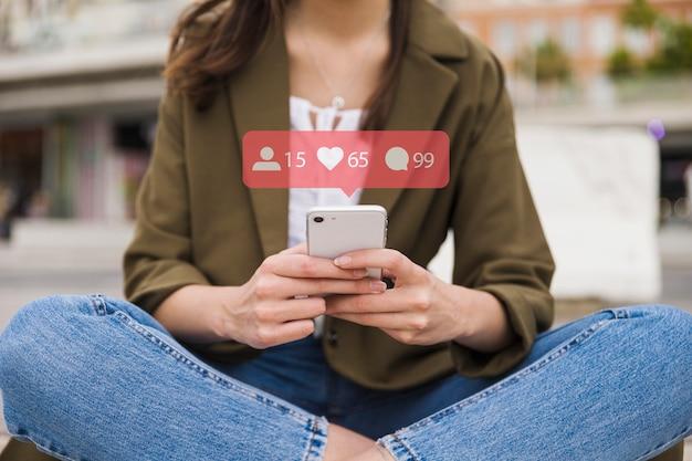 Nahaufnahme der frau mobiltelefon mit social media-netzikonen halten Kostenlose Fotos