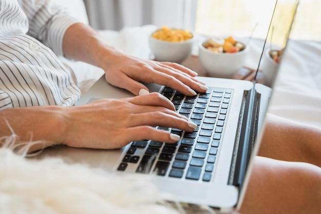 Nahaufnahme der frau schreibend auf laptop mit frühstück auf bett Kostenlose Fotos