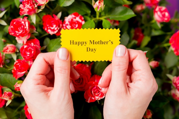 Nahaufnahme der frauenhände, die grußkarte mit glücklichem muttertag des textes und schönem blumenstrauß der rosa roten rosensprührosenblumen halten. muttertagskonzept. Premium Fotos