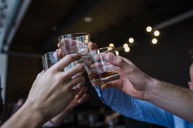 Nahaufnahme der freundhand, die toast mit glas whisky anhebt Kostenlose Fotos