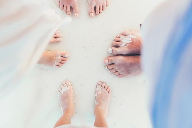Nahaufnahme der füße der familie auf dem weißen sandstrand Premium Fotos