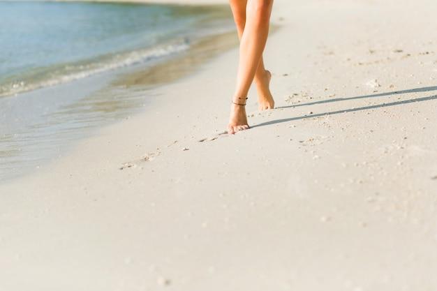 Nahaufnahme der gebräunten schlanken mädchenfüße im sand. sie geht in der nähe des wassers. sand ist gold Kostenlose Fotos