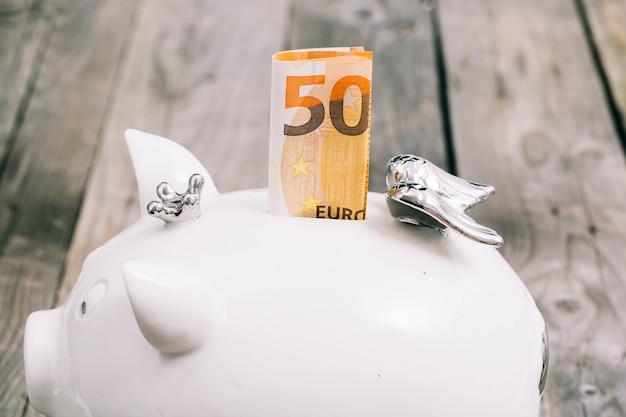 Nahaufnahme der gefalteten anmerkung des euro fünfzig im schlitz des weißen sparschweins Kostenlose Fotos