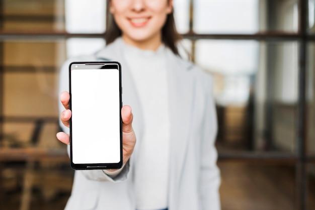 Nahaufnahme der geschäftsfrauhand mobiltelefon des leeren bildschirms im büro zeigend Kostenlose Fotos