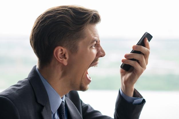 Nahaufnahme der geschäftsmann am smartphone schreien Kostenlose Fotos