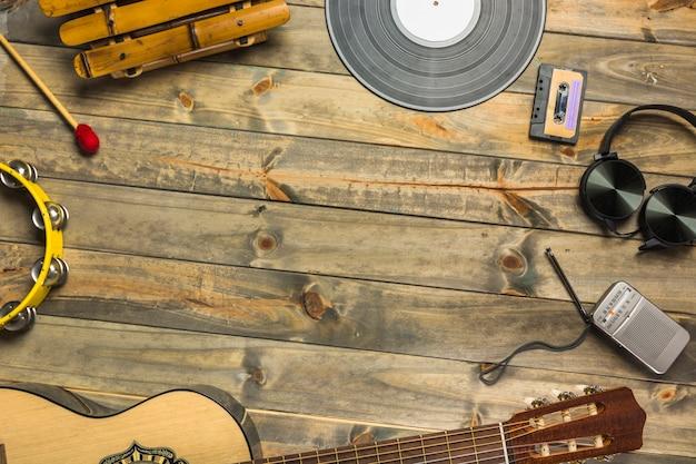 Nahaufnahme der gitarre; kopfhörer; tambourin; xylophon; kopfhörer und radio auf holztisch Kostenlose Fotos